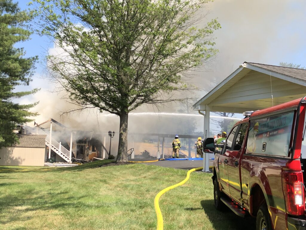 Photo of firefighters putting out a fire in a home